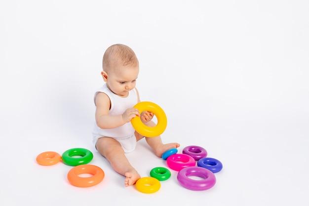 Menino bonito, 8 meses de idade, brincando com uma pirâmide em uma parede branca isolada, desenvolvimento precoce de crianças