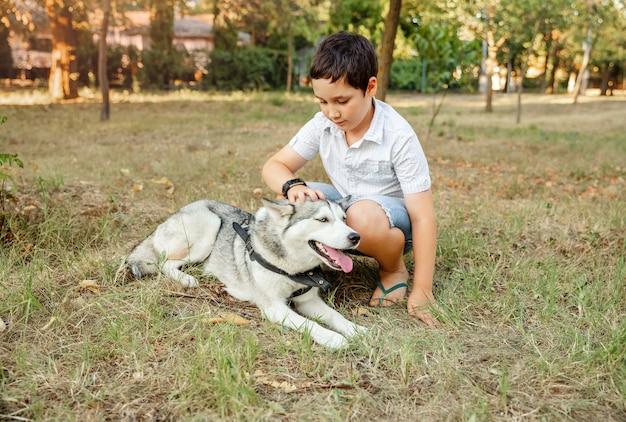 Menino bonito abraçando seu cachorro no parque de verão. melhores amigos descansam