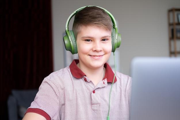 Menino bonito adolescente em fones de ouvido, estudando online, jogando videogame usando laptop sentado na cozinha.