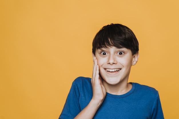Menino bonito animado, com os olhos bem abertos e o sorriso largo, surpreso com as boas novas, segurando a mão na bochecha, muito feliz e espantado, sobre o pano de fundo amarelo. conceito de emoções de pessoas.