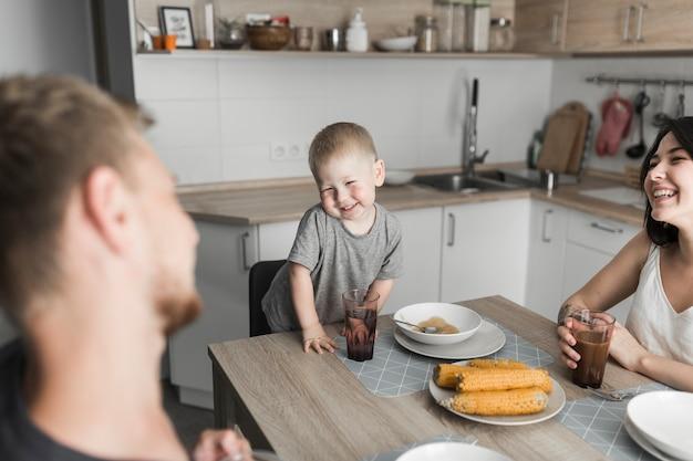 Menino bonito, aproveitando o café da manhã com seus pais na cozinha