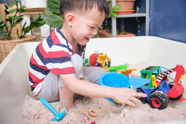 Menino bonito asiático brincando com areia sozinho em casa.
