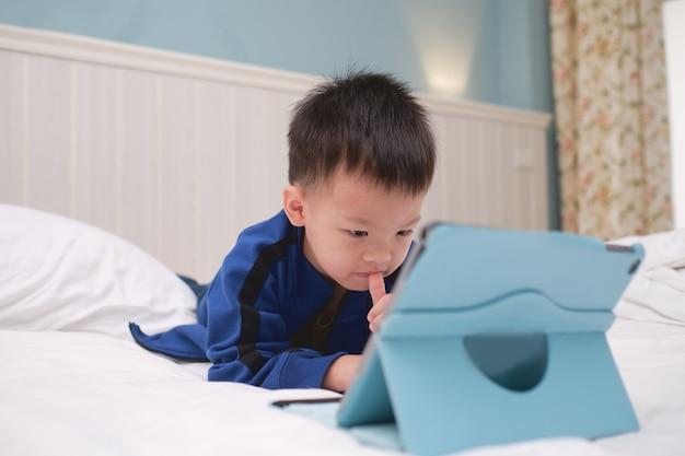 Menino bonito asiático de 3 a 4 anos de idade sorrindo enquanto joga, assistindo desenhos animados, usando o computador tablet pc, crianças viciadas em gadgets, learning tablet for kids, conceito de brinquedo educacional para crianças