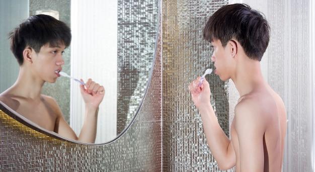 Menino bonito asiático escovando os dentes na frente do espelho de manhã.
