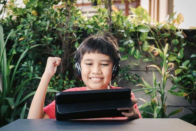 Menino bonito asiático usando fones de ouvido sem fio e sorrindo alegremente enquanto joga no tablet.