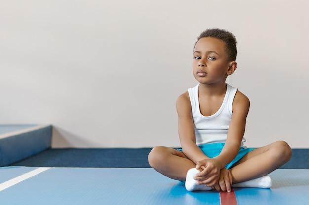 Menino bonito, atlético, de pele escura, de dez anos, com roupas esportivas elegantes, tendo aula de educação física