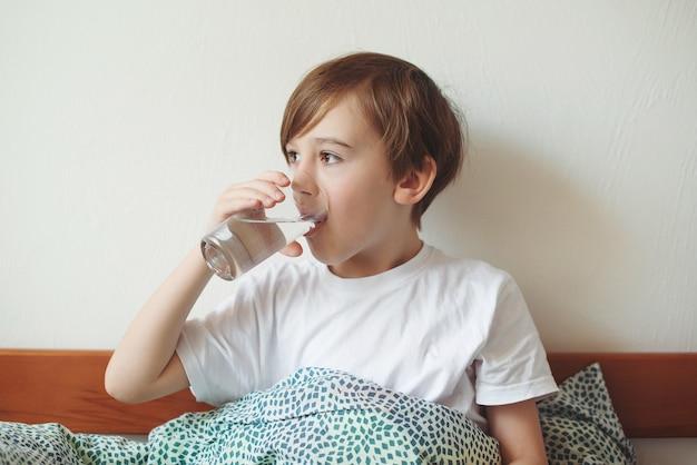 Menino bonito, bebendo água doce na cama em casa e o aluno segurando um copo de água pura pela manhã.