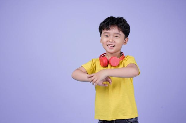 Menino bonito bonito e asiático com fone de ouvido e música