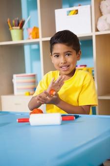 Menino bonito brincando com argila de modelagem na sala de aula