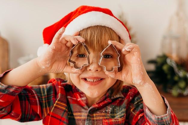 Menino bonito brincando com formas de biscoitos de natal