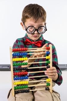 Menino bonito, brincando com o ábaco contra o quadro branco na sala de aula
