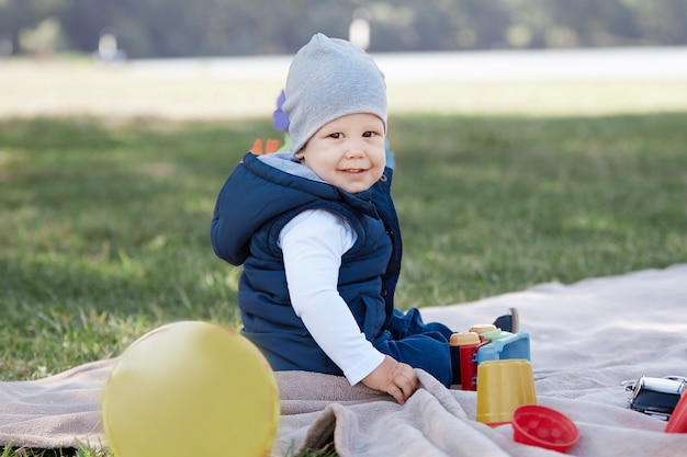Menino bonito brincando com um carrinho de brinquedo sentado no gramado do parque