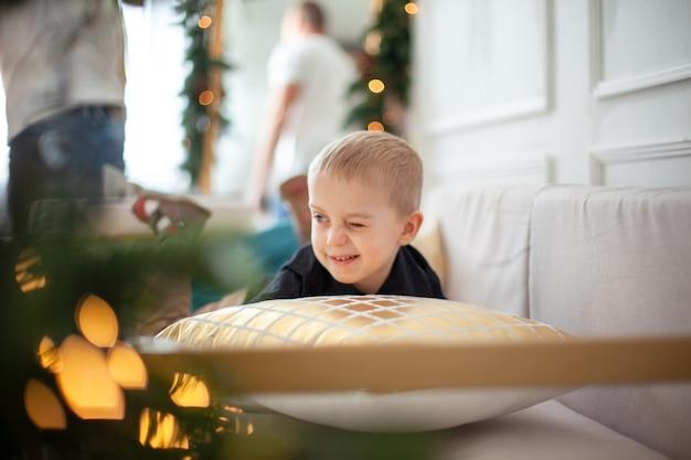 Menino bonito brincando com um travesseiro, se escondendo atrás dele, sorrindo e se divertindo em um cenário de natal.