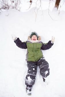 Menino bonito brincar com neve no parque. espírito de natal