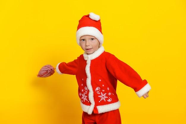 Menino bonito caucasiano acenando um saco de presentes em um fundo amarelo vestido de papai noel.