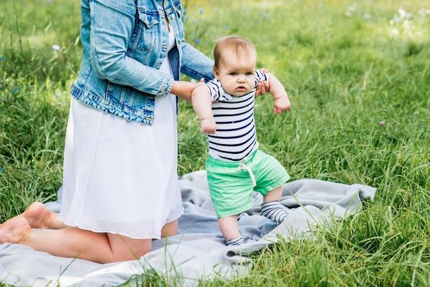 Menino bonito, caucasiano, camiseta listrada. piquenique no parque de verão. primeiros passos.