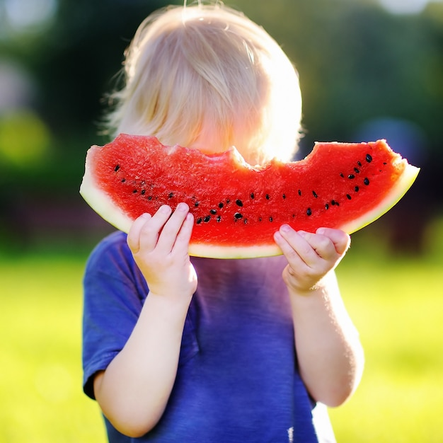 Menino bonito caucasiano com comer melancia fresca