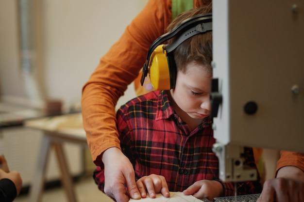 Menino bonito, caucasiano, com fones de ouvido, esculpindo uma árvore de natal de madeira com uma serra de fita na marcenaria