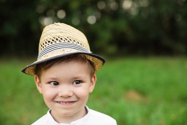 Menino bonito, caucasiano, com roupas elegantes, passeando