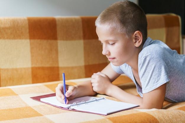 Menino bonito, caucasiano, deitado no sofá, desenha em um caderno com uma caneta ou faz sua lição de casa para a escola ...