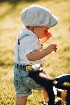 Menino bonito, caucasiano, em roupas elegantes, caminhando para o jardim com os pais