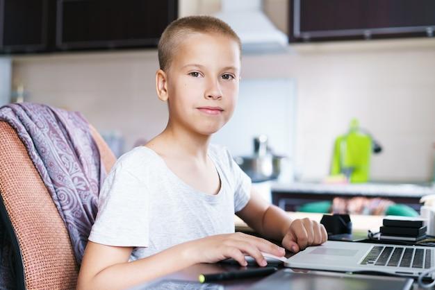 Menino bonito, caucasiano, sentado à mesa usando o computador para comunicação por videoconferência com o professor