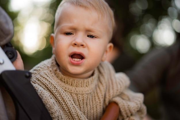 Menino bonito, caucasiano, sentado em um carrinho de bebê, assustado ou chateado