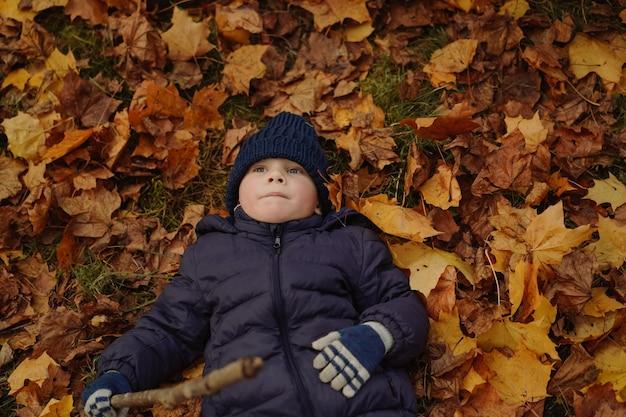 Menino bonito caucasiano sorridente deitado no chão coberto com folhas de bordo amarelas em um parque segurando um