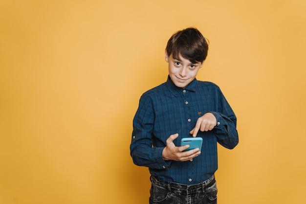 Menino bonito caucasiano sorrindo, vestindo camisa casual e calça jeans, apontando para a tela do telefone pelo dedo indicador, sobre o pano de fundo amarelo. novo aplicativo instalado.