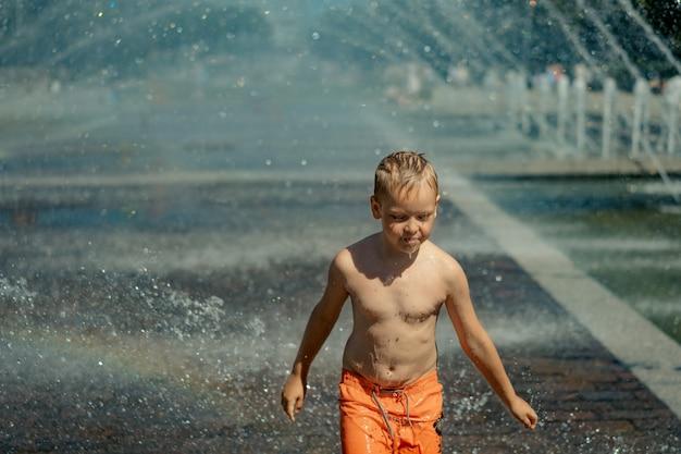 Menino bonito, caucasiano, usando calção de banho laranja, correndo em uma floresta