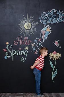 Menino bonito, cheirando a flor no quadro de giz preto