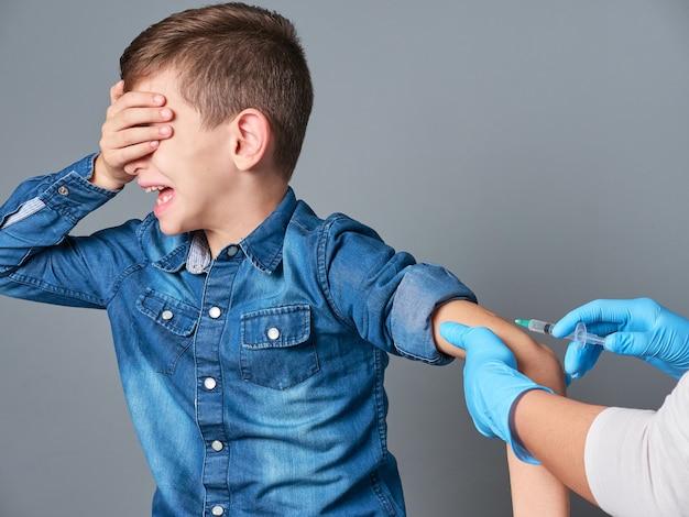 Menino bonito chorando enquanto é vacinado isolado em cinza