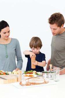 Menino bonito colocando sal e pimenta em sua salada na cozinha