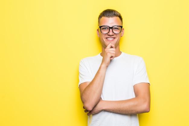 Menino bonito com a mão sob o queixo vestido com uma camiseta branca e óculos transparentes
