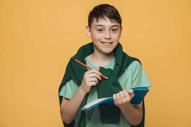 Menino bonito, com olhos castanhos, vestido com uma camiseta verde e um suéter verde escuro amarrado no pescoço, mantém seu diário fazer avisos para um dia seguinte, posando o conceito de educação.