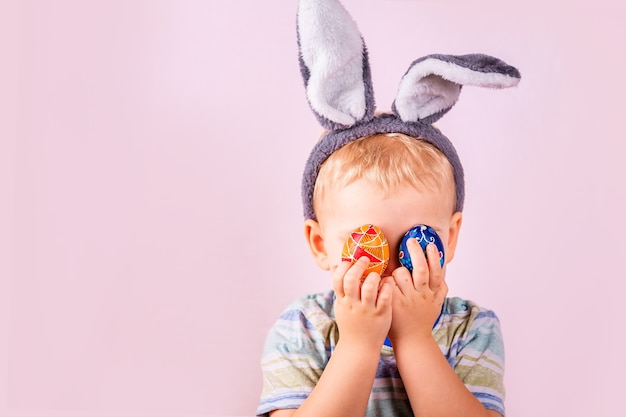 Menino bonito com orelhas de coelho na cabeça, fechando os olhos com ovos coloridos no fundo rosa.