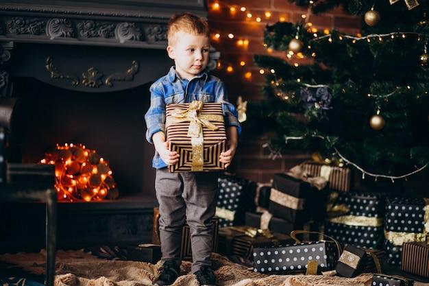 Menino bonito com presente de natal pela árvore de natal