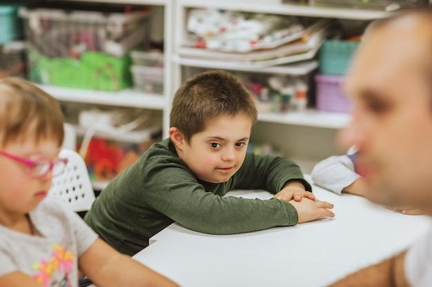 Menino bonito com síndrome de down, camisa verde, sentado na mesa branca com outras crianças e estudando