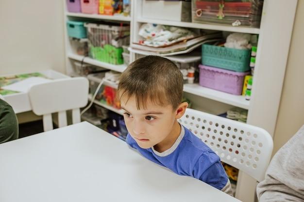 Menino bonito com síndrome de down em uma camisa azul, sentado na mesa branca e estudando
