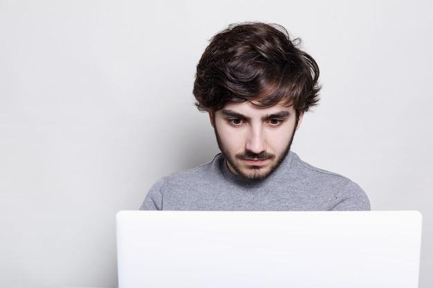 Menino bonito com um penteado elegante e barba da moda, olhando com espanto para a tela do seu computador portátil