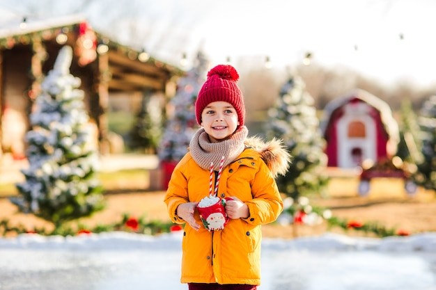 Menino bonito com uma jaqueta laranja na pista de gelo