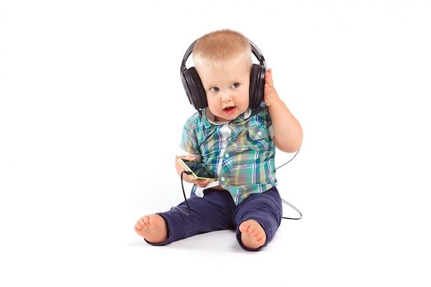 Menino bonito confuso com fones de ouvido