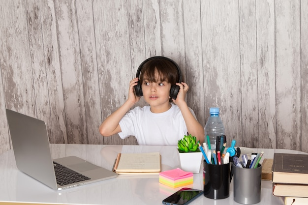 Menino bonito criança em fones de ouvido de camiseta branca preta usando laptop cinza em cima da mesa junto com planta verde