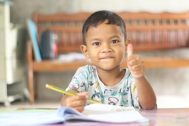 Menino bonito criança estudando e pensando em casa.