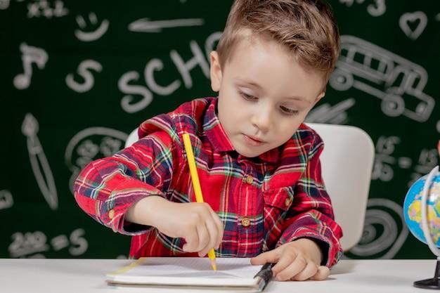Menino bonito criança fazendo lição de casa. garoto inteligente, desenho na mesa. estudante. aluno da escola primária de desenho no local de trabalho. garoto gosta de aprender. educação escolar em casa. de volta à escola. garotinho na lição da escola