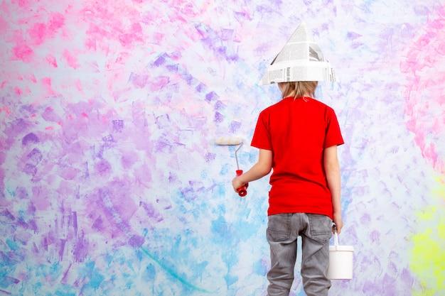 Menino bonito criança vista traseira em t-shirt vermelha e calça jeans cinza, pintando a parede colorida