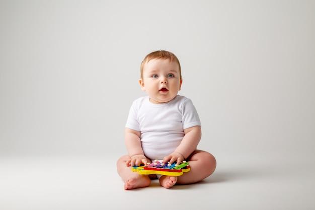 Menino bonito da criança 8 meses de idade em bodysuit branco brinca com o desenvolvimento de sessão de brinquedo