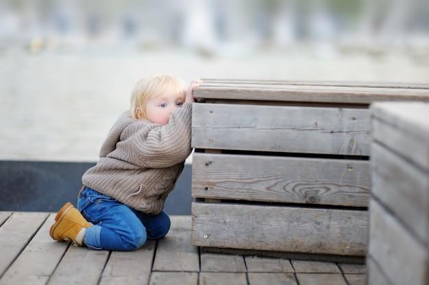 Menino bonito da criança brincar ao ar livre na primavera ou no dia de verão