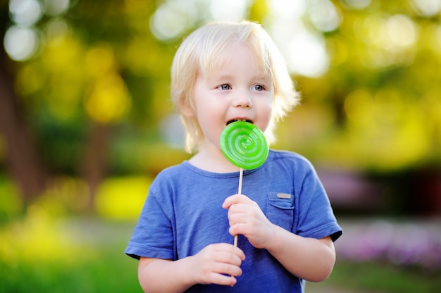 Menino bonito da criança com o pirulito verde grande. criança comendo doce barra de chocolate. doces para crianças e jovens. diversão ao ar livre de verão