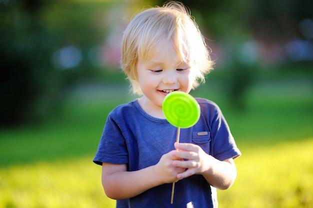 Menino bonito da criança com o pirulito verde grande. criança comendo doce barra de chocolate.
